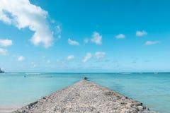 道路步行方式墙壁延伸到干净的蓝色海在好蓝色云彩天空假日 免版税库存图片