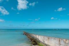 道路步行方式墙壁延伸到干净的蓝色海在好蓝色云彩天空假日 免版税图库摄影