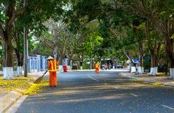道路清扫工清洁有笤帚工具和簸箕的城市边路 免版税库存照片