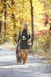 道路的女孩穿过秋天的森林 免版税图库摄影