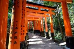 道路穿过红色torii门行在Fushimi Inari-taisha的在京都,日本 免版税库存照片