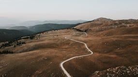 道路穿过谷在日落采取的山脉顶部 JPG 免版税库存照片