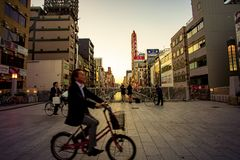 道顿堀大阪日本- november6,2018通过dotonbori桥梁,dotonbori的未认出的人骑马自行车是一个多数pupular 免版税图库摄影