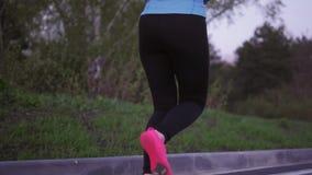 遗弃情人的 蓝色体育衣裳的一个女孩沿晚上公园跑 回到视图 在运动鞋的女性腿关闭 股票录像