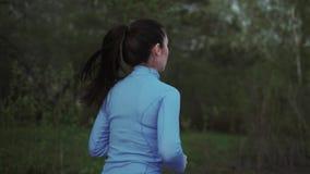 遗弃情人的 蓝色体育衣裳的一个女孩沿晚上公园跑 回到视图 影视素材