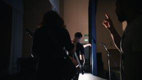 遗弃阶段和开始重复-一个人的一个年轻摇滚小组给握手独奏者 股票视频