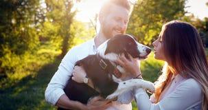 遛一对年轻的夫妇一条狗在公园 图库摄影