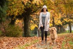 遛愉快的妇女她的金毛猎犬狗在有秋天的一个公园 免版税库存图片