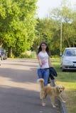 遛的女孩一条狗在夏日 库存照片