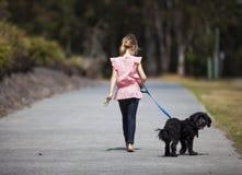 遛的女孩她的狗 免版税库存照片