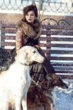 遛的妇女在街道上的一条狗在冬天 库存照片