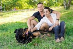 遛美好的夫妇一条狗在公园 在夫妇的焦点 免版税库存图片