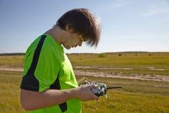 遥控为quadrocopter,特写镜头 控制移动的设备的在男性手上,被弄脏的自然发射机 免版税图库摄影