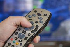 遥控的电视和手 免版税库存图片