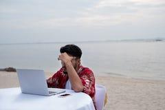 遥远地工作在海滩的年轻商人 商人wor 免版税库存照片