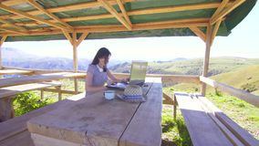 遥远地研究在山的一台膝上型计算机的女孩自由职业者 股票视频