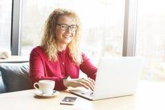 遥远地研究她时兴的膝上型计算机的美丽的少妇在行家咖啡店 有时髦腕子的愉快的女性自由职业者 库存图片