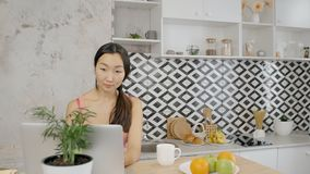遥远地研究膝上型计算机的美丽的亚裔妇女在厨房里 股票视频