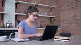 遥远的工作,镜片的年轻女性在剪贴板写笔记和键入在膝上型计算机键盘在坐在的慢动作 影视素材