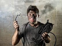 遭受与肮脏的被烧的面孔的未受训练的人缆绳电子事故在滑稽的震动表示 免版税库存图片
