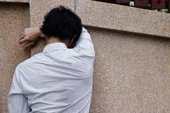 遭受严厉消沉的沮丧的沮丧的年轻亚裔商人背面图  免版税库存图片