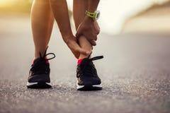 遭受体育伤害的赛跑者,当跑在城市街道上时 库存照片