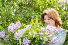 遭受关于开花的丁香的偏头痛的妇女 库存照片