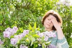 遭受关于开花的丁香的偏头痛的妇女 免版税库存照片