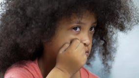 遭受唐氏综合症坐在桌上,医疗保健的沮丧的女孩 免版税库存图片