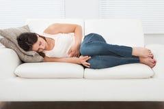 遭受在沙发的stomachache的妇女 免版税库存照片