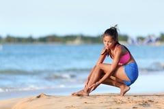 遭受在海滩赛跑的脚腕痛苦的慢跑者 免版税库存照片