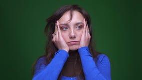遭受在绿色背景的偏头痛的沮丧的深色的女实业家画象  影视素材