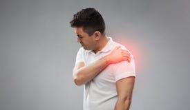 遭受在肩膀的痛苦的不快乐的人 免版税库存照片