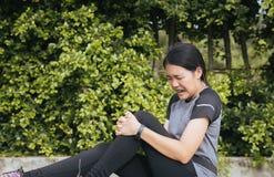 遭受在腿的痛苦的亚洲妇女赛跑者被伤害,接触她的膝盖的手在跑步以后 免版税图库摄影
