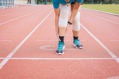 遭受在腿的痛苦的亚洲妇女赛跑者被伤害,接触她的膝盖的手在跑步和锻炼以后室外在轨道runni 免版税库存照片