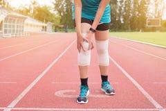 遭受在腿的痛苦的妇女赛跑者在跑跑步以后被伤害,接触她的膝盖的手 免版税库存照片