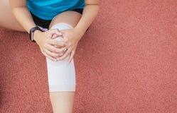 遭受在腿的痛苦的妇女赛跑者被伤害,接触她的在轨道赛跑的手kneeafter跑步和锻炼 库存图片