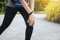 遭受在腿的痛苦的妇女赛跑者被伤害,接触她的膝盖的手在跑步以后 免版税库存照片