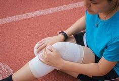 遭受在腿的痛苦的妇女赛跑者被伤害,接触她的膝盖的手在跑步在轨道赛跑以后 库存照片