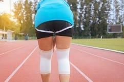 遭受在腿的痛苦的妇女赛跑者被伤害,接触她的膝盖的手在跑步在轨道赛跑以后 免版税库存照片