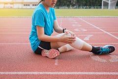 遭受在腿的痛苦的妇女赛跑者被伤害,接触她的kneeafter跑步和锻炼的手室外 免版税库存图片