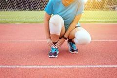 遭受在腿的痛苦的运动员妇女有脚腕的在室外跑跑步和的锻炼以后被伤害 免版税图库摄影