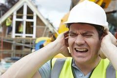 遭受在建筑工地的噪音污染的建筑工人 免版税库存图片