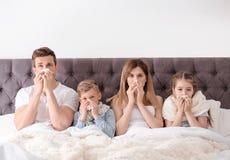 遭受寒冷的家庭在床上 免版税图库摄影