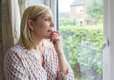 遭受广场恐怖症的哀伤的妇女看在窗口外面 免版税库存照片