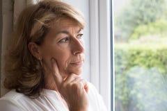 遭受广场恐怖症的哀伤的妇女看在窗口外面 库存照片