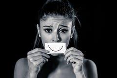 遭受消沉的少妇掩藏她的悲伤和哀痛在拉长的微笑后 免版税库存图片
