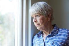 遭受消沉的资深妇女看在窗口外面 免版税库存图片