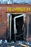 遭受火房子 弯曲的前门 灰烧了炭烬热红色保持的木柴片段 检查灭火器的人 免版税库存照片
