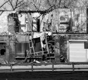 遭受火房子 灰烧了炭烬热红色保持的木柴片段 火灾危险 单色 库存照片